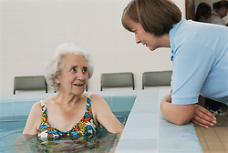 Elderly patient in hydrotherapy pool speaking to physiotherapist,
