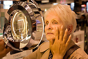 "An elderly lady receives a consultation from a professional beautician in the Clinique Bar at World Duty Free in Heathrow Airport's Terminal 5. In a quiet corner of peace and tranquility, the woman's face is examined in detail using a magnifying lens that allows the assistant to see every hair follicle and pore. Amid the busy departures terminal of this international aviation hub, this is a corner of quiet and tranquillity before the woman traveller boards her flight after this few minutes of pampering. From writer Alain de Botton's book project ""A Week at the Airport: A Heathrow Diary"" (2009)."
