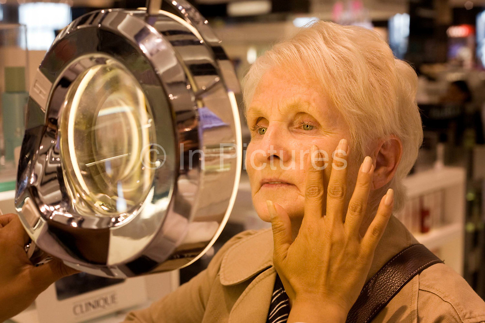 """An elderly lady receives a consultation from a professional beautician in the Clinique Bar at World Duty Free in Heathrow Airport's Terminal 5. In a quiet corner of peace and tranquility, the woman's face is examined in detail using a magnifying lens that allows the assistant to see every hair follicle and pore. Amid the busy departures terminal of this international aviation hub, this is a corner of quiet and tranquillity before the woman traveller boards her flight after this few minutes of pampering. From writer Alain de Botton's book project """"A Week at the Airport: A Heathrow Diary"""" (2009)."""