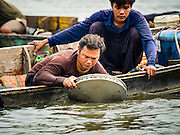 06 OCTOBER 2015 - BANGKOK, THAILAND: A dive team on a salvage diver's boat rinses off a pan full of scrap metal he brought up from the bottom of the Chao Phraya River in Bangkok. Divers work in two man teams on small boats in the Chao Phraya River. One person stays in the boat while the diver scours the river bottom for anything that can be salvaged and resold. The divers usually work close to shore because the center of the river is a busy commercial waterway with passenger boats and commercial freight barges passing up and down the river all day long. The Chao Phraya is a dangerous river to dive in. It's deep, has large tidal fluctuations, is fast flowing and badly polluted. The divers make money only when they sell something.     PHOTO BY JACK KURTZ