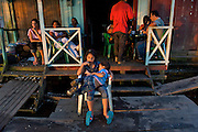 A family takes in sunset from their dockside storefront - Puerto Narino - Amazonas - Colombia