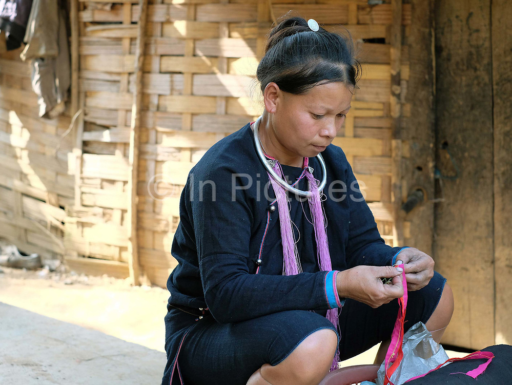 A Lanten ethnic minority woman sews traditional clothing outside her home, Ban Houey Liey, Luang Namtha province, Lao PDR. The Lanten or Yao Mun are a small but distinctive group of the Yao ethnic minority residing in northern Laos, Vietnam and China. Maintaining a strong cultural identity, they are easily recognised by their hand woven, indigo dyed attire. Unlike many other ethnic groups who have relinquished their traditional dress, each Mun family still cultivates cotton and indigo for spinning, weaving, dyeing and sewing into clothing. One of the most ethnically diverse countries in Southeast Asia, Laos has 49 officially recognised ethnic groups although there are many more self-identified and sub groups. These groups are distinguished by their own customs, beliefs and rituals.