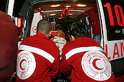 Emergency medical transport staff lift a patient on a stretcher out of an ambulance into the Al Maqassad hospital in Jerusalem. Médecins Du Monde (MDM) and the Palestine Red Crescent Society (PRCS) have set up emergency transport and community first aid training in the West Bank since the Wall was built and has cut off easy access to Jerusalem hospitals.