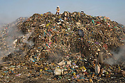 Smokey Mountain rising above. A mound of garbage which began its life in the 1960's as a landfill site...RUBBISH DUMP RECYCLING. South East Asia, Cambodia, Phnom Penh. Smokey Mountain, Steung Mean Chey, is Phnom Penh's municipal rubbish dump. Thousands work there, some 600 minors and 2000 adults, recycling the city's rubbish, dumped there by garbage trucks every day. The dump is notorious as many very young children work there. People eat and sleep overnight in the rubbish and fumes, under plastic tarpaulins or in the open air. They work 24 hours a day, like miners, with headlamps at night, collecting plastic, metals, wood, cloth & paper, which they sort and clean, weigh and sell, to be carried away for recycling. A day's work typically brings less than a dollar per person. One and a half to two dollars per day per family. The overpowering, acrid odour of grey smokey fumes blows across the dump, from which the place gets its name 'Smokey Mountain'. It can be smelt miles away. The shantytowns and squats, the recycling worker's homes butt onto or are inside the dump itself. There is no running water, sanitation and many are ill. Children often work with friends or relatives. Religious and ngo's help some children, but this is often resisted by families who need the extra income they generate.///Using fire to separate metal from plastic and rubber, a recycling worker takes advantage of the permanently burning rubbish.