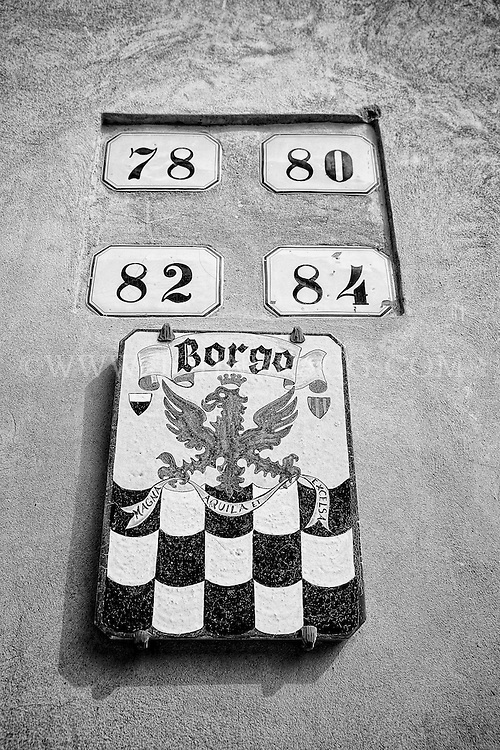 Black and white image of apartment signage in San Quirico d'Orcia, Italy.