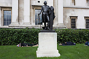 Homeless men sleep beneath the statue of US President George Washington in London's Trafalgar Square. The sleeping males are seen stretched across the lawn outside the National Gallery as America's first president looks important and statesmanlike, a symbol of pioneering freedom and success whereas the men are symptomatic of poverty and failure. The George Washington is a replica of a work by Jean-Antoine Houdon.