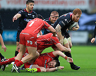 Dan Baker of the Ospreys is stopped by Ken Owens © and Rob Evans (on ground) of the Scarlets. Guinness Pro12 rugby match, Ospreys v Scarlets at the Liberty Stadium in Swansea, South Wales on Saturday 26th March 2016.<br /> pic by  Andrew Orchard, Andrew Orchard sports photography.