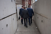 Businessmen negotiate concrete blocks where a construction site disrupts pedestrians walking through the City of London, England UK.