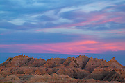A band of wispy clouds turns pink at dusk over the Badlands in this view over the White River Valley, Badlands National Park, South Dakota.