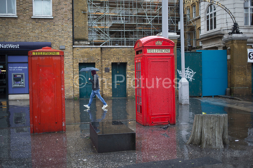 Two different designs of the red telephone box on a wet rainy day on Whitechapel Road, London, UK. The different phone boxes originate from totally differing eras.