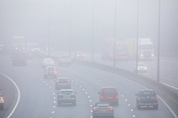 © Licensed to London News Pictures. 07/12/2020. Surrey, UK. Commuters drive through dense fog on the M25 in Leatherhead, Surrey as the Met Office issue a yellow weather warning for freezing fog with disruption to transport for the South East of England this morning. The Government is expected to rolling out the new Pfizer/BioNTech's coronavirus vaccine tomorrow with reports it has already arrived in the UK for distribution to hospitals around the country. Photo credit: Alex Lentati/LNP