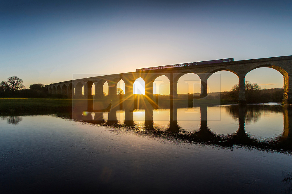 © Licensed to London News Pictures. 20/02/2018. Arthington UK. The 07:27 from Horsforth to Pannal crosses Arthington viaduct at sunrise this morning in Yorkshire. Photo credit: Andrew McCaren/LNP