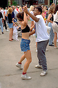 Interracial couple age 25 dancing at Grand Old Day street festival.  St Paul Minnesota USA