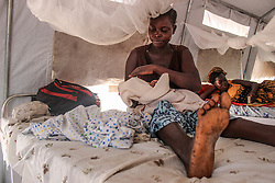 A woman holds her new born at the maternity ward. BidiBidi settlement in Northern Uganda, is now the third largest refugee settlement in the world. It currently holds more than 210,000 South Sudanese refugees escaping from war, and the ongoing influx of a daily average of 3,000 refugees is causing a strain on humanitarian aid and funding.