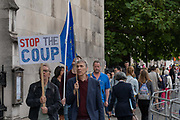 A man holds a Stop The Coup placard as anti-Brexit campaigners gather outside Houses of Parliament on the first day after summer recess on 3rd September 2019 in London in the United Kingdom. MPs return to Westminster for a Brexit shutdown that could result in a general election.