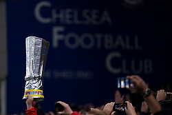 Chelsea fans in the stands hold up a replica Europa League trophy