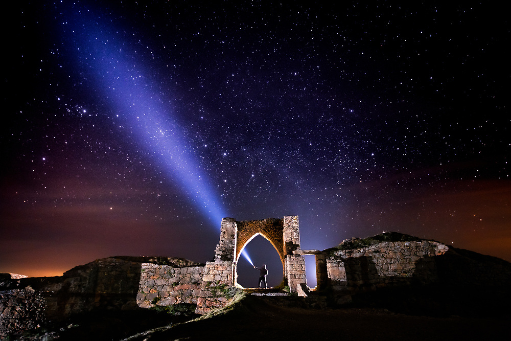 Grosnez Castle, the tourist attraction and historic ruins owned by the National Trust, lit up under a star filled sky in Jersey, Channel Islands