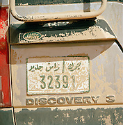 Detail of Libyian number plate covered in sand, Sahara Desert, Libya