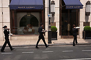 Staff carry a covered buffet lunch, across a road in central London and towards a business event around the corner on 7th June 2016. The smartly-dressed trio wearing black all walk in unison along the street just off Bond Street and each carry two salvers of sandwiches and other snack.
