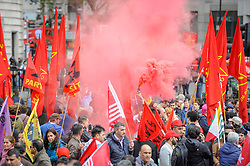 © Licensed to London News Pictures. 01/05/2017. London, UK. Demonstrators taking part in the annual May Day Rally on International Workers' Day light a flare as they arrive for a rally in Trafalgar Square.   Photo credit : Stephen Chung/LNP