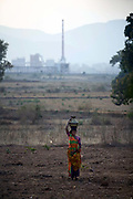 A Dongria Kondh Tribal woman carries a pot of water on her head in front of the Vedanta plant, Lanjigargh, Orissa, India. The Dongria Kondh are a protected 'Scheduled' Caste of Original (aboriginal) people that practice animism and live a settled rural life. Their deity is a mountain from which a mining company, Vedanta is seeking to extract bauxite which will largely destroy the mountain and the Kondh's traditional way of life.