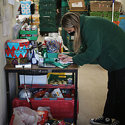 Workers and volunteers at Hackney Foodbank receive and organize food donations, 15th of December 2021, Hackney, East London, United Kingdom. Food donated is weighed in and registrered. The Hackney Foodbank is part of a nationwide network of foodbanks, supported by The Trussell Trust, working to combat poverty and hunger across the UK. The food bank gives out three days emergency food supplies to families and individual who go hungry in the borrough. The food is all donated by individuals and the food donated is held in a small ware house where it is  sorted and packed for distribution.  More people than ever in Britain have turned to the food bank for help and in Hackney the need has gone up with 350% over the past two years.