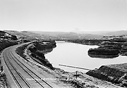 9305-B7012-3. The Columbia river at Big Eddy. The entrance to the Celilo Canal is on the right. The Seufert cannery is in the background on the left, Seufert's No. 2 fishwheel is on the point in the center of the image. The Dalles Dam was built in the center of this picture. Taken about 1930.