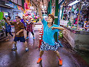 11 AUGUST 2016 - BANGKOK, THAILAND:   A woman works out in an aerobics class in Pak Khlong Talat, better known as the Bangkok Flower Market. Public exercise classes are common throughout Thailand. Most of the participants in the exercise class in the Bangkok flower market are older adults, although the class is open to everyone.       PHOTO BY JACK KURTZ