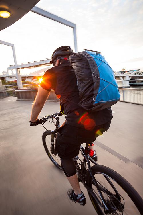 Commuting cylcist on the Kurilpa Bridge, Brisbane.