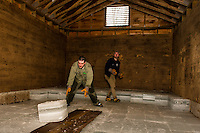 Chris Burrows and Alex Sands precisely position ice blocks as they slide into the Rockywold Ice House during the ice harvest on Wednesday.  The two ice houses at Rockywold-Deephaven Camp will be full to the rafters (approximately 10-11 layers) after the three day ice harvest.  (Karen Bobotas/for the Laconia Daily Sun)