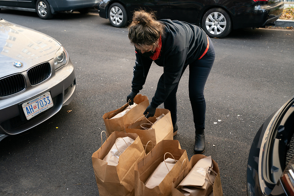 Marina Ivanova, 45 and Assistant General Manager of Medium Rare, carries meals into Columbia Heights Community Center in Washington, DC on Wednesday, November 25th, 2020. Medium Rare chef and owner Mark Bucher's organization Feed the Fridges provides free daily restaurant-made meals in public refrigerators across Washington, DC.