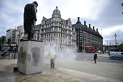 """© Licensed to London News Pictures. 08/06/2020. London, UK. A cleaner removes Graffiti from a statue of former British Prime Minister Winston Churchill in Parliament Square, after it was graffitied with the words """"was a racist"""" during a Black Lives Matter demonstration In central London. The death of George Floyd, who died after being restrained by a police officer In Minneapolis, Minnesota, caused widespread rioting and looting across the USA. Photo credit: Ben Cawthra/LNP"""