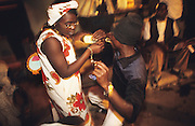 Youths drinking hard alcohol in discotheque in the Kano ghettos. Sex, drugs, rock and Roll and alcohol are outlawed under Sharia Law but exist anyway..The implementation of Islamic Sharia Law across the twelve northern states of Nigeria, centres upon Kano, the largest Muslim Husa city, under the feudal, political and economic rule of the Emir of Kano. Islamic Sharia Law is enforced by official state apparatus including military and police, Islamic schools and education, plus various volunteer Militia groups supported financially and politically by the Emir and other business and political bodies. Fanatical Islamic Sharia religious traditions  are enforced by the Hispah Sharia police. Deliquancy is controlled by the Vigilantes volunteer Militia. Activities such as Animist Pagan Voodoo ceremonies, playing music, drinking and gambling, normally outlawed under Sharia law exist as many parts of the rural and urban areas are controlled by local Mafia, ghetto gangs and rural hunters. The fight for control is never ending between the Emir, government forces, the Mafia and independent militias and gangs. This is fueled by rising petrol costs, and that 70% of the population live below the poverty line. Kano, Kano State, Northern Nigeria, Africa