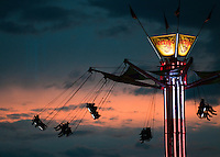 Carnival riders enjoy a final night of thrills as the sun sets over Jackson Hole and the Teton County Fair.