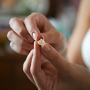 A Bride holds a charm of her new initial, before her autumn Maine wedding.