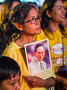 05 DECEMBER 2014 - BANGKOK, THAILAND: A woman holds a picture of Bhumibol Adulyadej, the King of Thailand, during birthday celebrations for the King. Thais marked the the King's 87th birthday Friday. The King was born on December 5, 1927, in Cambridge, Massachusetts. The family was in the United States because his father, Prince Mahidol, was studying Public Health at Harvard University. He has reigned since 1946 and is the world's currently reigning longest serving monarch and the longest serving monarch in Thai history. Bhumibol, who is in poor health, is revered by the Thai people. His birthday is a national holiday and is also celebrated as Father's Day. He is currently hospitalized in Siriraj Hospital, recovering from a series of health setbacks.     PHOTO BY JACK KURTZ