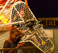 August 7, 2012 - Merrick, New York, U.S. - Riding the Zipper, a high spinning ride, a teen girl screams in metal cage as young boy leaving ride walks past, on the first night of the 22nd Annual Merrick Festival on Long Island.
