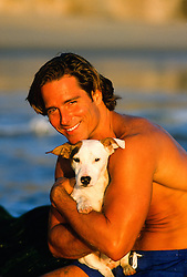 All American man at the beach with a Jack Russell puppy