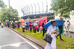 Licensed to London News Pictures. 28/06/2021. London, UK. Tennis fans brave the rain on the first day of Wimbledon. Long queues form outside the All England Lawn Tennis Club in Wimbledon, southwest London today on the first day of the Championships as weather forecasters predict thunderstorms and showers for the next three days. The 2021 AELTC Tennis Championships at Wimbledon, southwest London is back today for the first time in two years after it was cancelled last year due to the Covid-19 pandemic. However, capacity is down by 50% and fans must pre-ordered tickets with no overnight camping. Photo credit: Alex Lentati/LNP