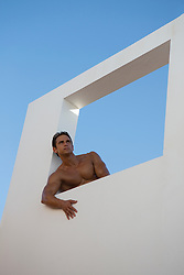 sexy shirtless man in an open framed window outdoors
