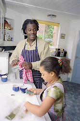 Single father and young daughter doing washing up in kitchen,