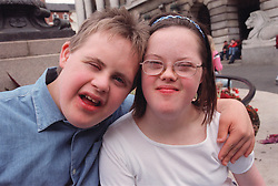 Portrait of teenage boy and girl with Downs Syndrome standing together hugging,
