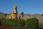 Cabazon Dinosaurs, also referred to as Claude Bell's Dinosaurs, are enormous, sculptured roadside attractions located in Cabazon, California. Mr. Rex, hiding behind the hedge, is a 100-ton tyrannosaurus rex concrete structure.