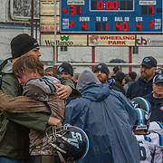 Former Timberwolves linebacker Owen Porter embraces Tyson Hall (22) after the team's loss to the Martinsburg Bulldogs in the the Class AAA WVSSAC championship football game at Wheeling Park Stadium in Wheeling, W.V., on Saturday, December 01, 2018.