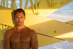 sexy shirtless man under a lifeguard stand at sunset