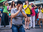 """31 DECEMBER 2012 - BANGKOK, THAILAND: A man prays at the Erawan Shrine at the Ratchaprasong Intersection on New Year's Eve. The traditional Thai New Year is based on the lunar calender and is celebrated in April, but the Gregorian New Year is celebrated throughout the Kingdom, especially in larger cities and tourist centers, like Bangkok, Chiang Mai and Phuket. Many Thais go to Buddhist temples and shrines to """"make merit"""" for the New Year. The Bangkok Countdown 2013 event was called ?Happiness is all Around @ Ratchaprasong.? All of the streets leading to Ratchaprasong Intersection were closed and the malls in the area stayed open throughout the evening.    PHOTO BY JACK KURTZ"""