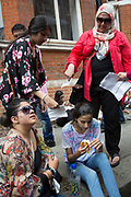 London, UK. Saturday 19th July 2014. Pro-Palestinian protesters in their tens of thousands march through central London to the Israeli Embassy in protest against the military offensive in Gaza by Israel. Girl who is fasting for Ramadan, passes out and is revived with water and a banana by her family as they wave paper to cool her down.