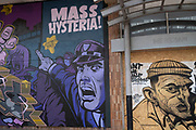 Mass hysteria street art graffiti on boarded up shops which are closed in Birmingham city centre due to the Coronavirus outbreak on 31st March 2020 in Birmingham, England, United Kingdom. Following government advice most people are staying at home leaving the streets quiet, empty and eerie. Coronavirus or Covid-19 is a new respiratory illness that has not previously been seen in humans. While much or Europe has been placed into lockdown, the UK government has announced more stringent rules as part of their long term strategy, and in particular social distancing.