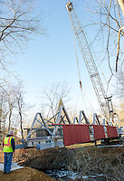Ron Mitchell guides the crane operator Mark Roberts as he maneuvers the bridge over the water in Belmont Village Monday afternoon.  (Karen Bobotas/for the Laconia Daily Sun)