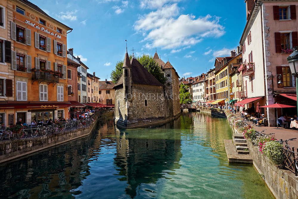 View of the Hôtel du Palais de I'Isle, and the Museum of Annecy and Cafe des Arts located in the cobblestone building along the Thiou Canal, old town Annecy, France